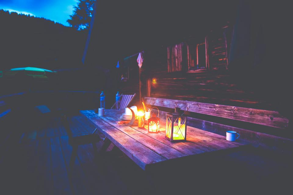 picnic table deck backyard outdoors night dark lanterns lights house cottage cabin