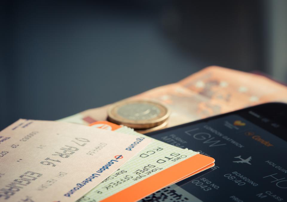 still items things passes boarding plane tickets coins currency bills gadgets smartphone mobile bokeh