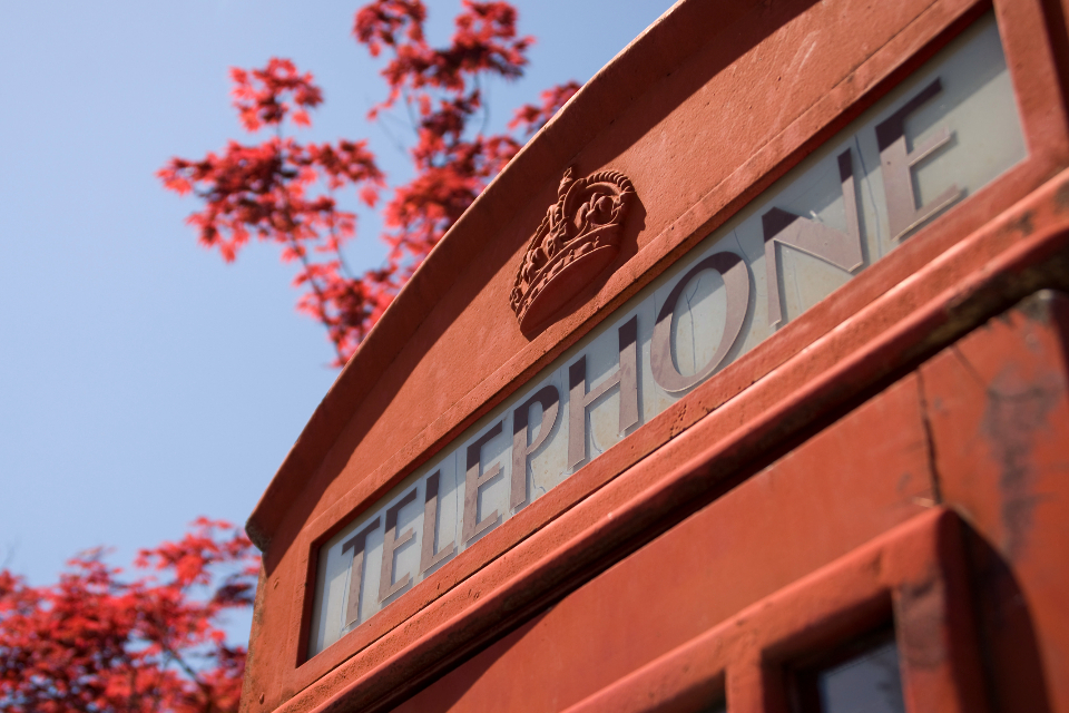 red telephone box london england blue sky plant