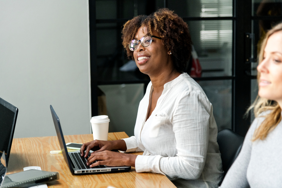african american businesswomen conference connection device digital diversity eyeglasses female hall happy hot drink ideas indoor internet laptop meeting modern network notebook notepad