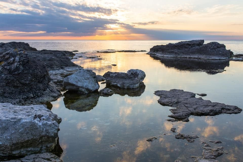 sea ocean water rock reflection nature horizon sunset sunrise sky clouds