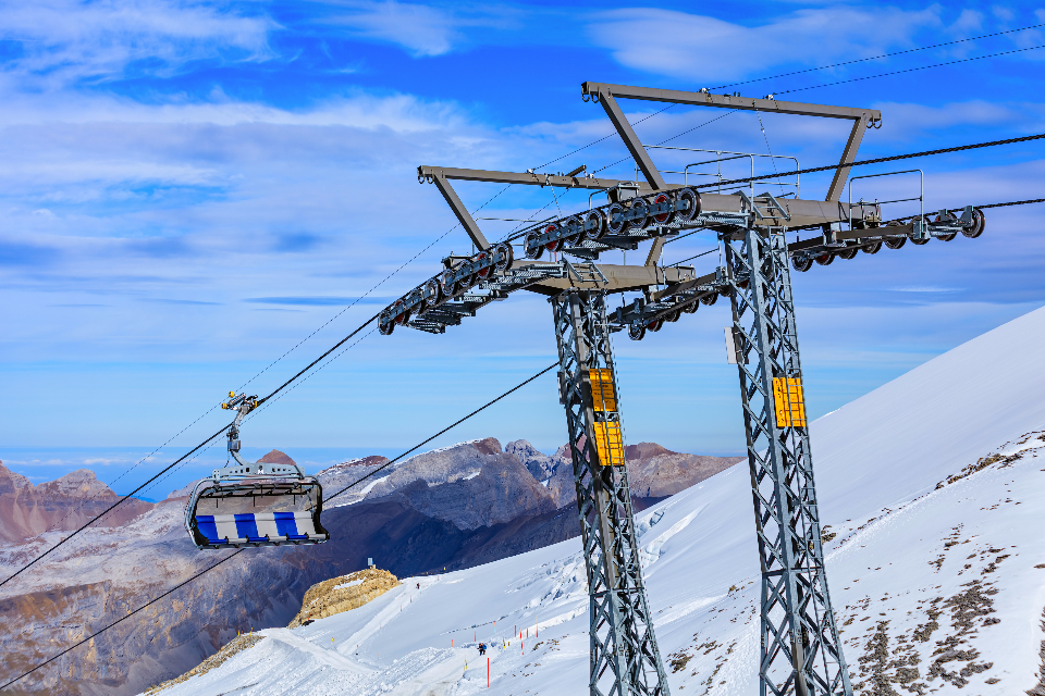 overhead cable car cable Titlis Switzerland cloudy cloud sky blue autumn mountain alpine Alps Swiss Alps summit peak Obwalden nature aerial scenics view travel travel destination landscape seat gondola snow slope Swi