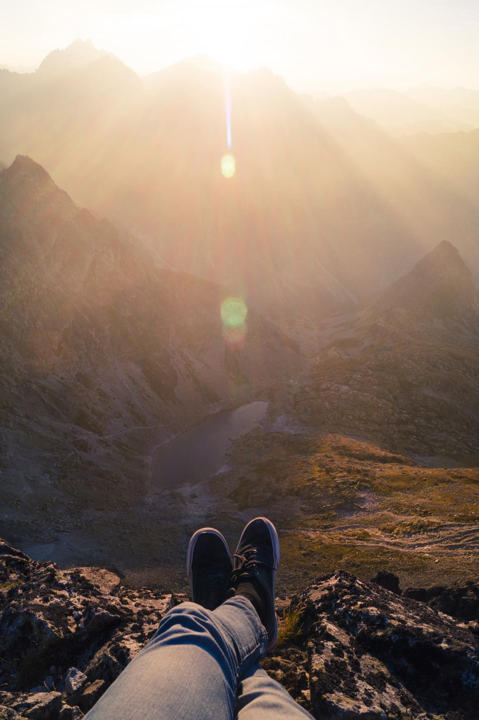 guy man male people feet legs shoes sneakers pants nature landscape mountains rocks lake sky solar flare sunlight