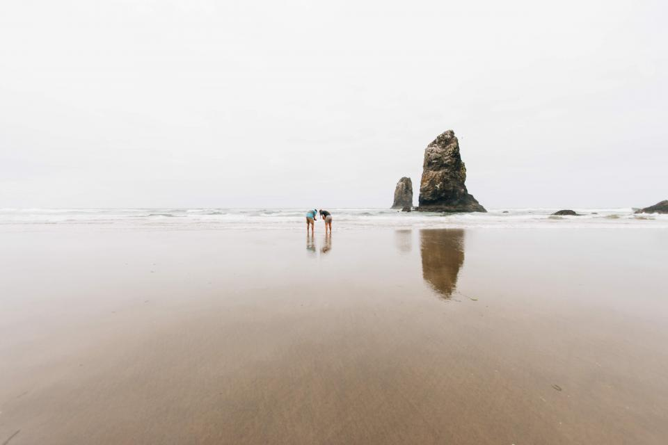 people rock formation sand beach shore water sea ocean waves travel trip vacation swim dive shells