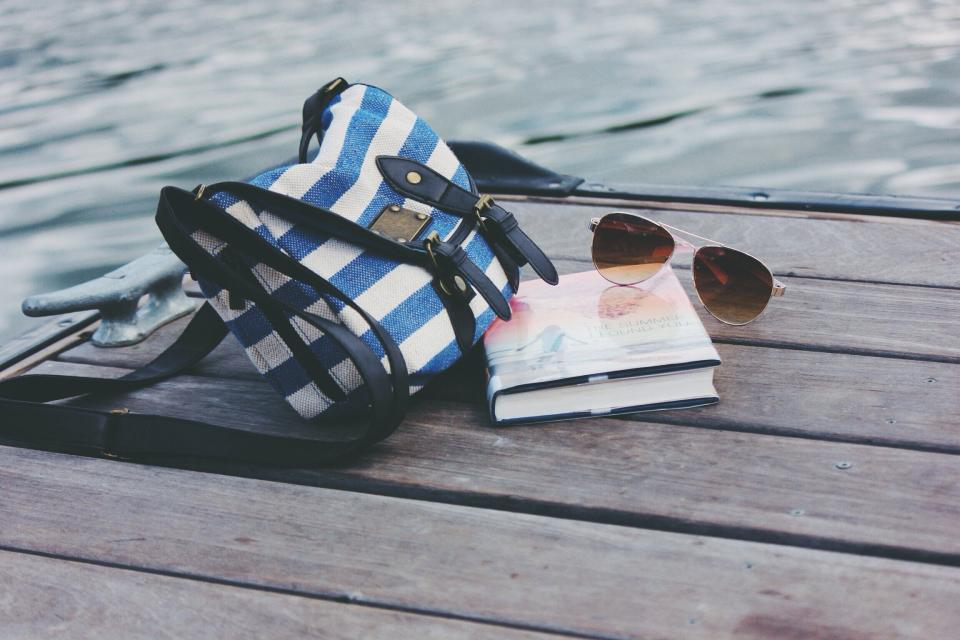 pier dock lake water sunglasses book objects purse bag purse outdoors