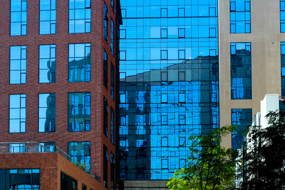 glass building city windows downtown urban architecture daytime business buildings modern reflection brick pattern blue sky offices