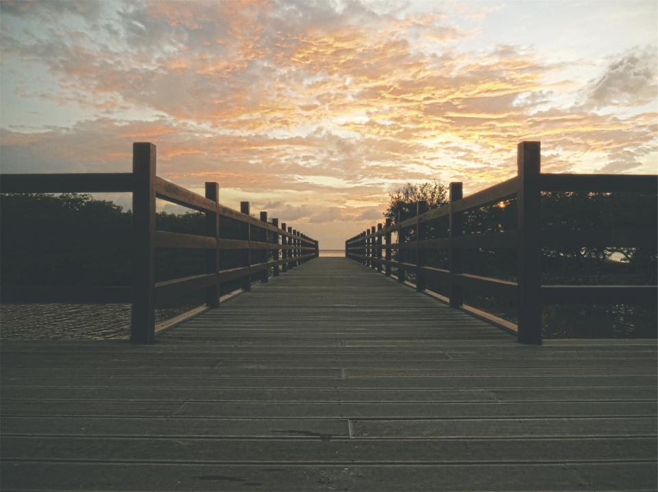 sunset sky clouds wood bridge railing beach ocean