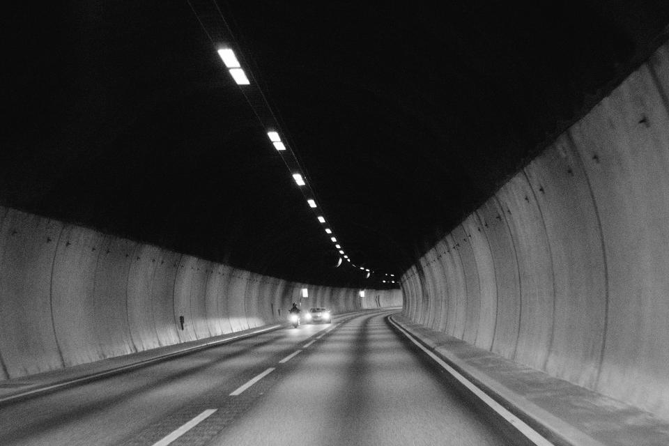 tunnel road pavement cars motorbike motorcycle lights black and white automotive