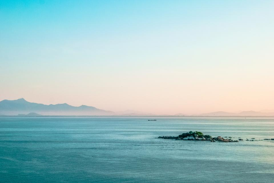 nature landscape water ocean sea waves rocks mountains view sky clouds horizon gradient blue pink