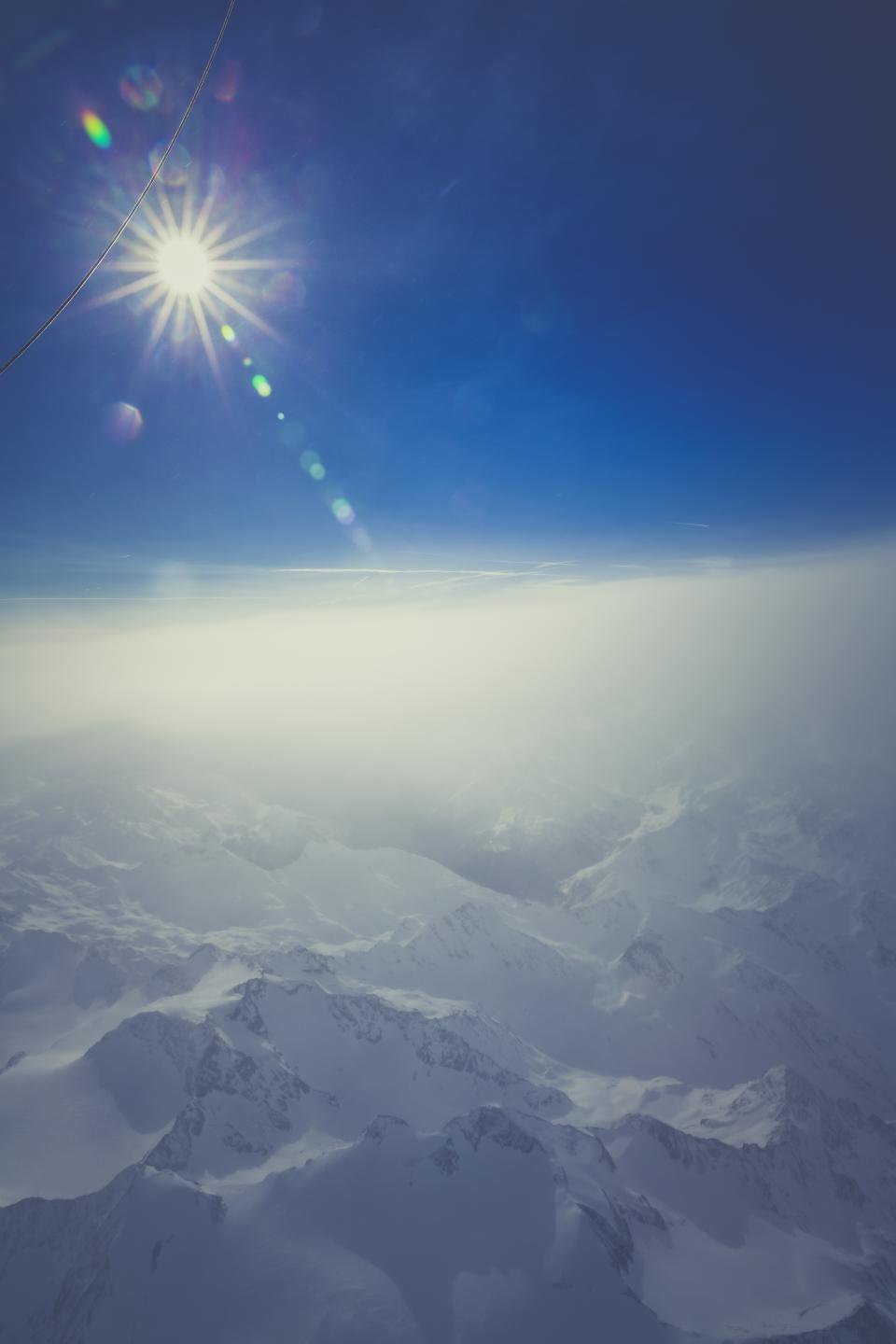 nature landscape mountains snow summit peaks aerial stratosphere sky clouds sun solar flare blue white