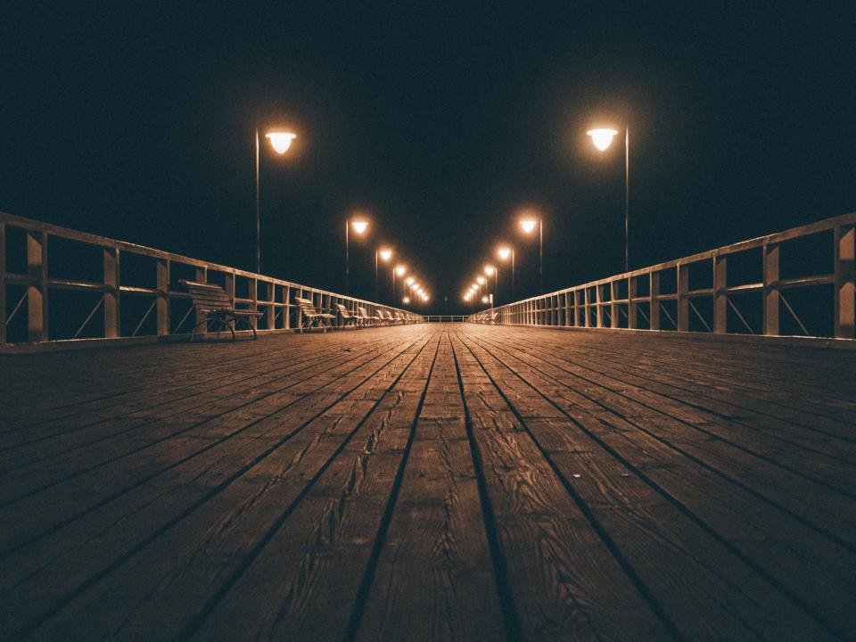 wood boardwalk pier dock night evening foggy railing lamp posts lights