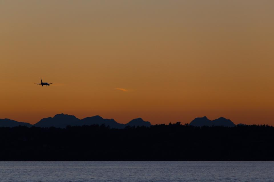 sunset dusk sky silhouette mountains landscape nature lake water airplane travel trip transportation