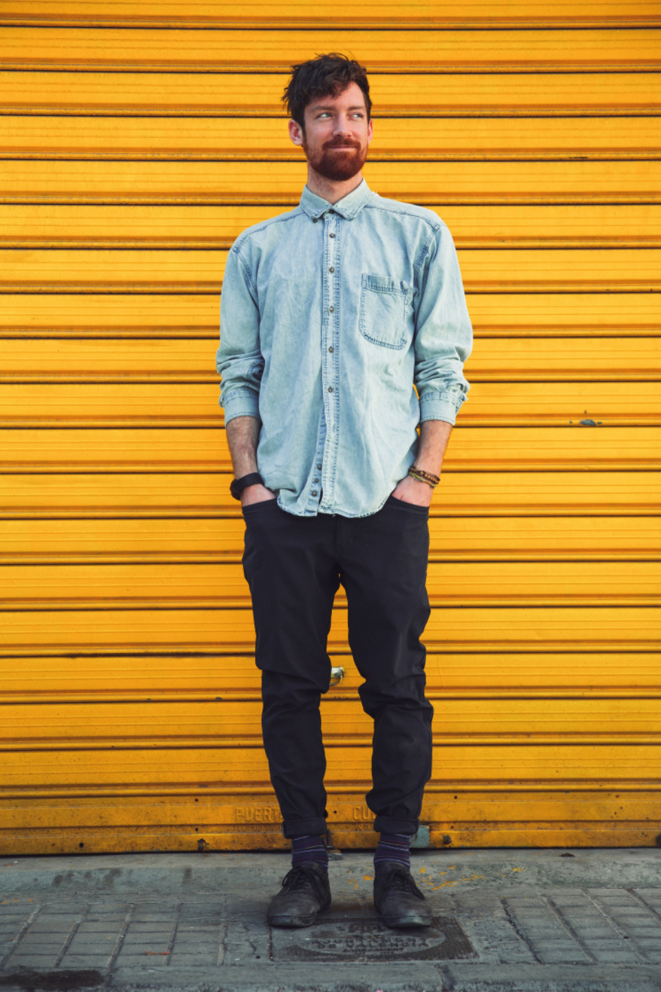 man smiling hipster pockets fashion yellow wall jeans shirt beard standing solo relaxed urban looking wristwatch