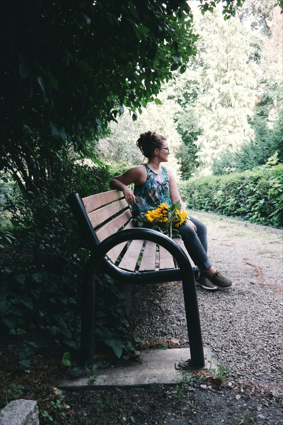 people girl sitting waiting alone bench nature flower trees green grass garden