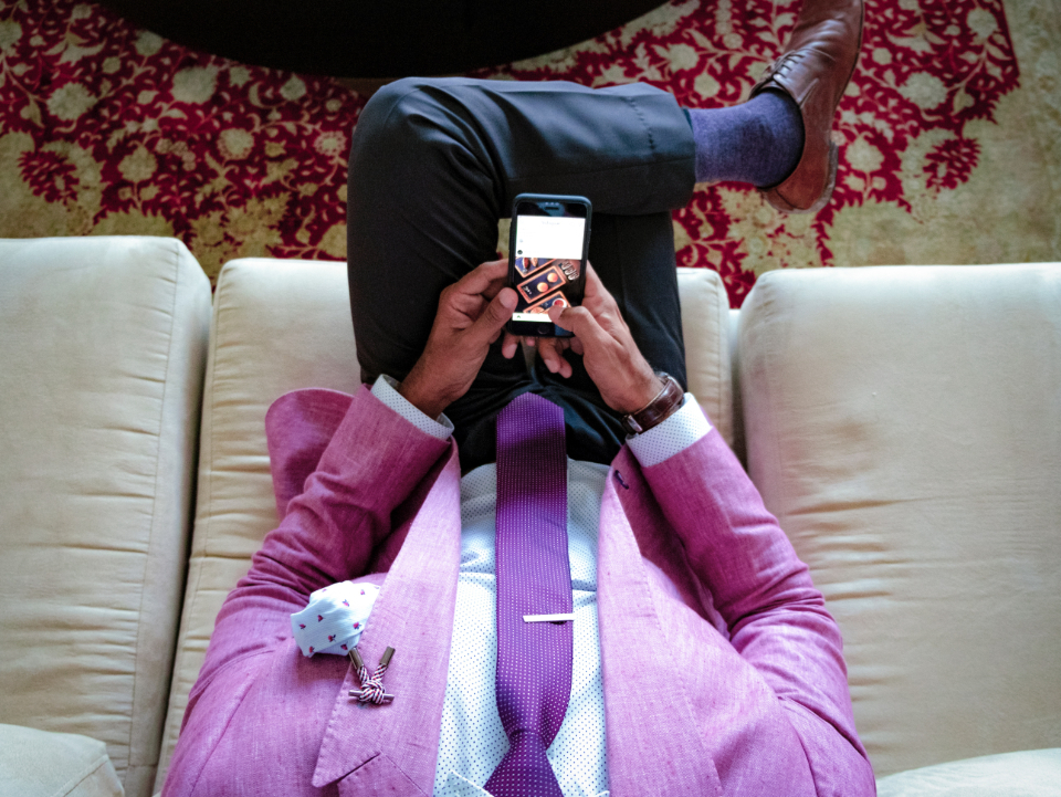 man pink suit mobile phone business technology people male sit couch type telephone tie pruple fashion style