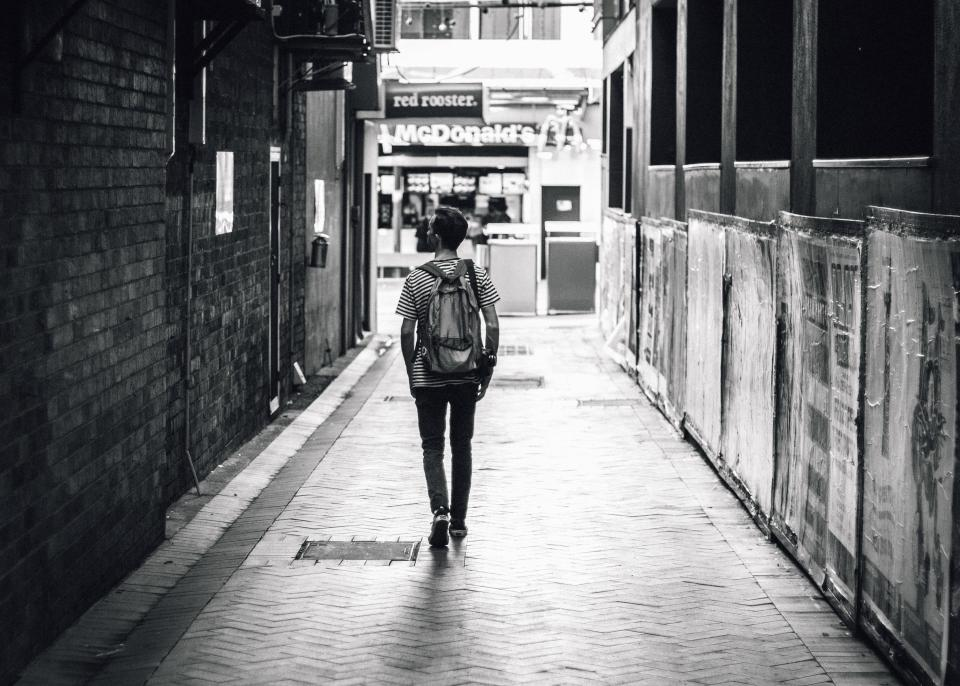 guy man walking backpack lifestyle pedestrian sidewalk alley city urban black and white