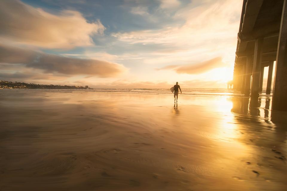 sea water beach people man surfing board sport sunlight sunset sunrise building infrastructure sky clouds