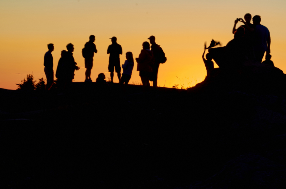 people mountain silhouette hiking tourists sunset travel adventure group trek landmark outdoor hill sky warm orange motion blur
