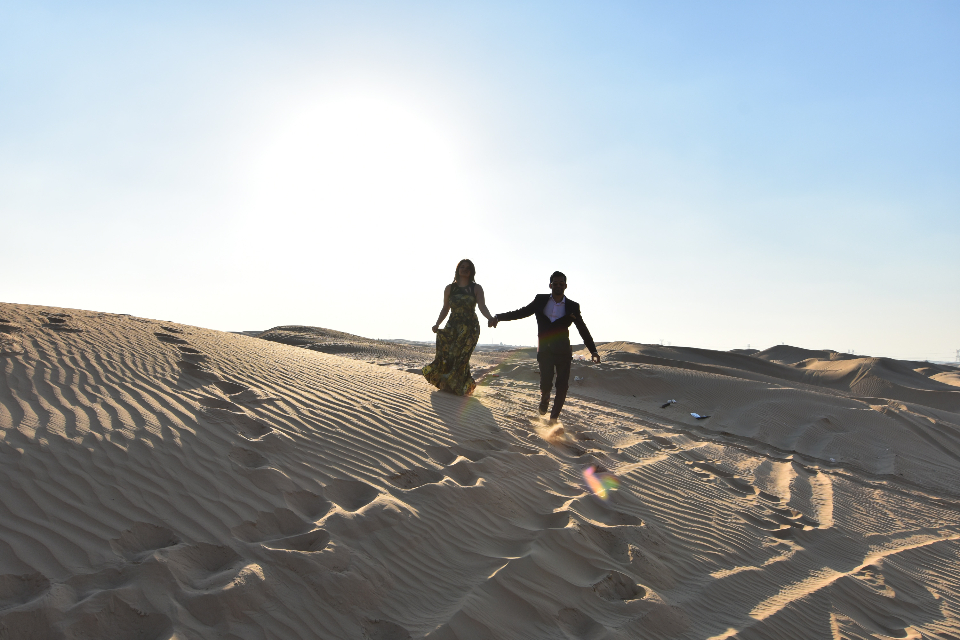 couple walking sand desert sand dune man woman love happy footsteps blue sky holding hands