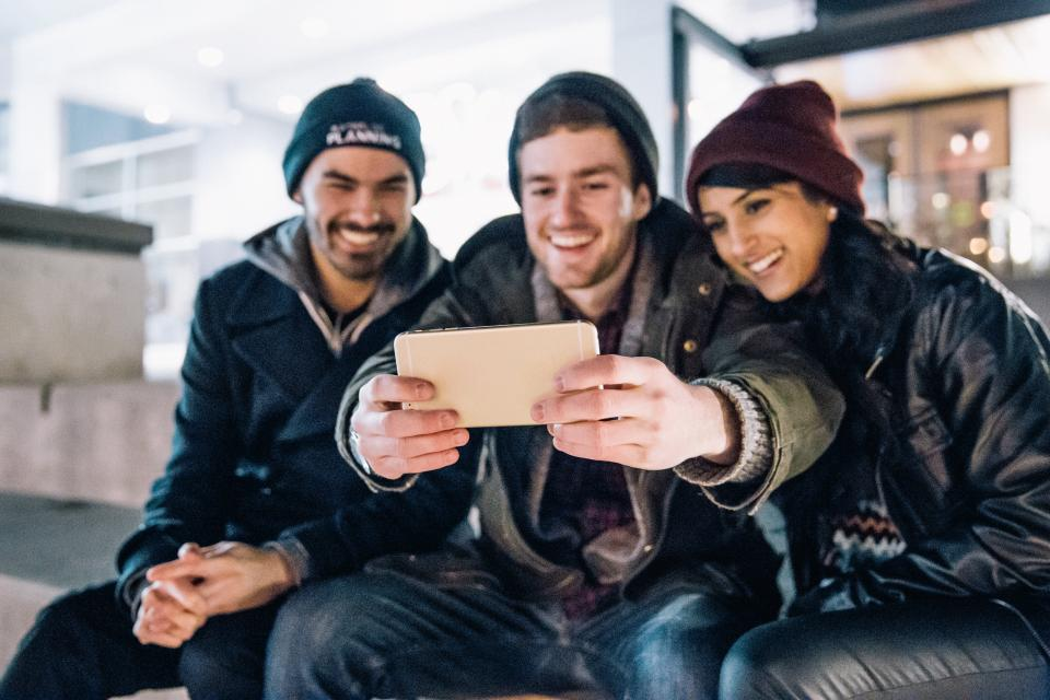people men guys boys girl woman friends sitting smile happy selfie camera photography mobile phone gadget electronics technology black leather jacket winter beanie