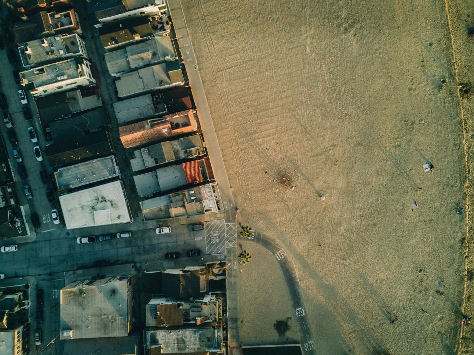 aerial view rooftops buildings aerial view road street car vehicle transportation field