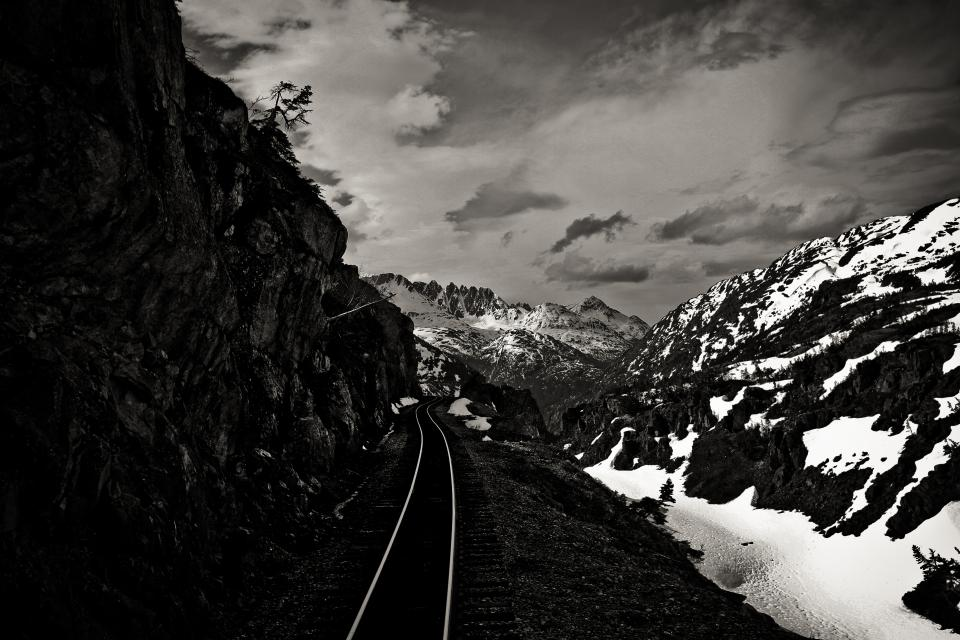 train tracks railroad railway transportation mountains cliffs snow clouds landscape black and white