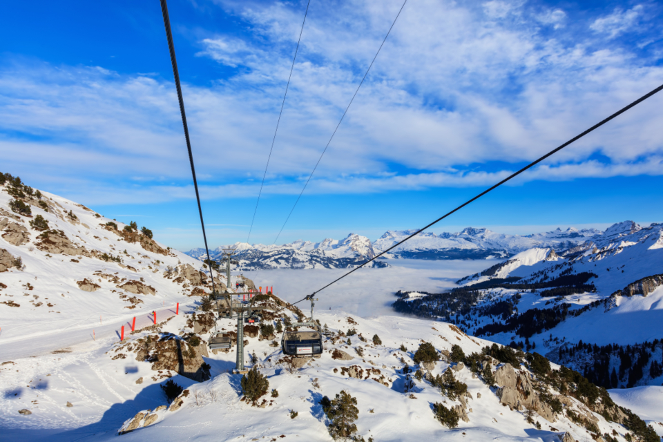 summit peak cliff slope cable car overhead cable car Swiss Alps Alps alpine landscape nature Fronalpstock mountain Schwyz Swiss Europe winter wintertime snow white blue sky Switzerland view cloud fog travel destination