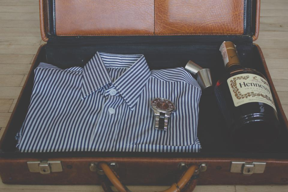 suitcase shirt clothes fashion watch Hennessy alcohol bottle leather objects
