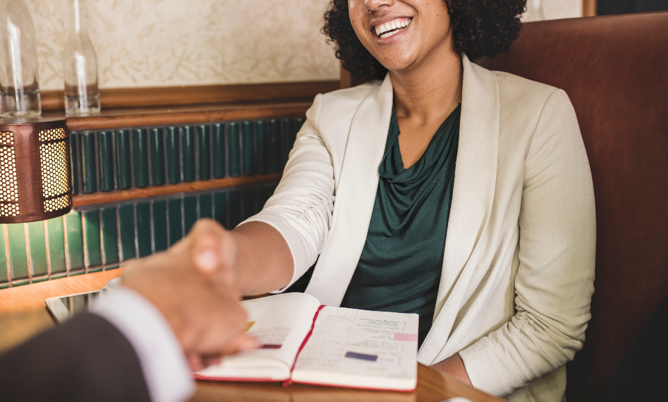 businesswoman meeting handshake achievement success african american black afro agreement business business deal cheerful happy smiling collaboration colleague corporate deal greeting hands help notes notepad notebook