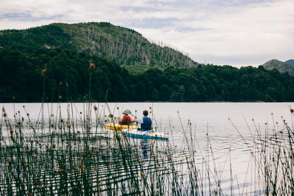 lake river water grass green trees mountain forest nature sky clouds people men boat sailing paddle