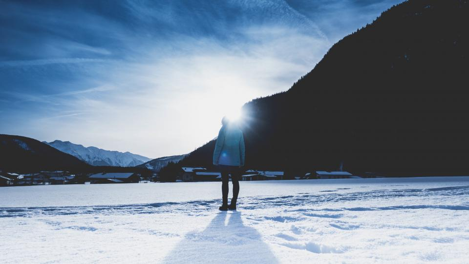 people man woman lady back sunshine rays shadow snow mountain houses village sky clouds winter