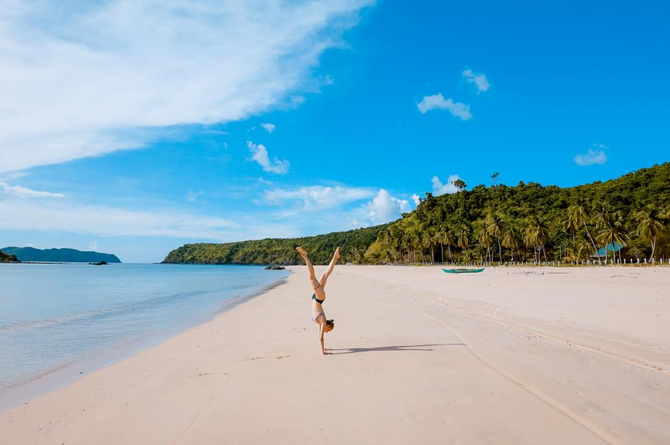 sea ocean water waves nature white sand beach coast shore people woman girl tumbling adventure fitness health exercise summer vacation swimming trees plants blue sky clouds