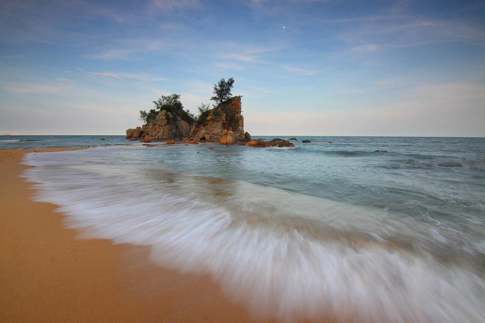 beach sand sea water hill rock formation nature sky clouds trees horizon vacation waves