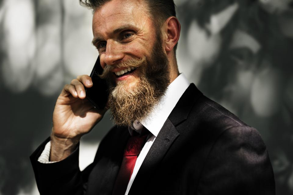 guy man people smile smiling happy mobile cell phone talking business suit tie moustache beard