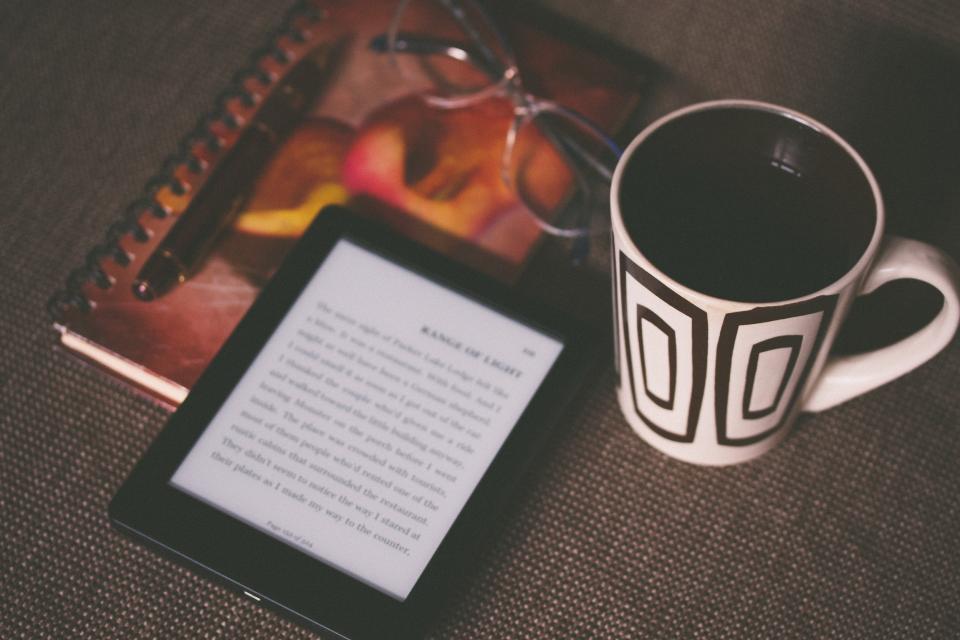 kindle e-reader technology reading book objects coffee cup mug notebook notepad pen eyeglasses business