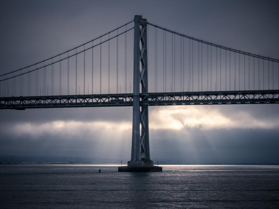 building infrastructure bridge sea ocean water dark clouds