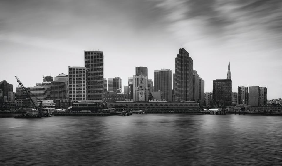 urban city establishment building structure infrastructure tower clouds sky black and white monochrome