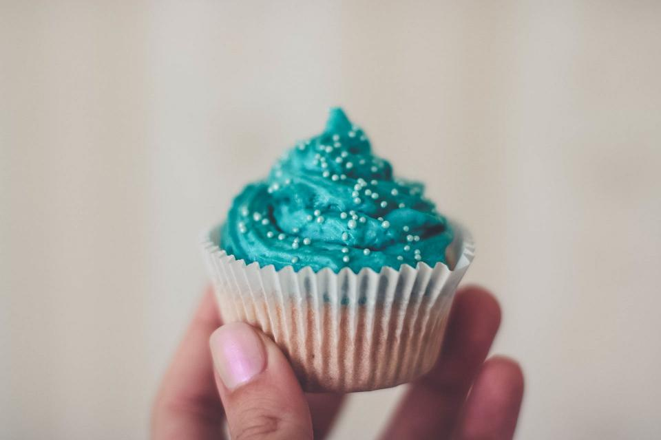 food eat gourmet cupcake icing blue hand fingers hold still bokeh