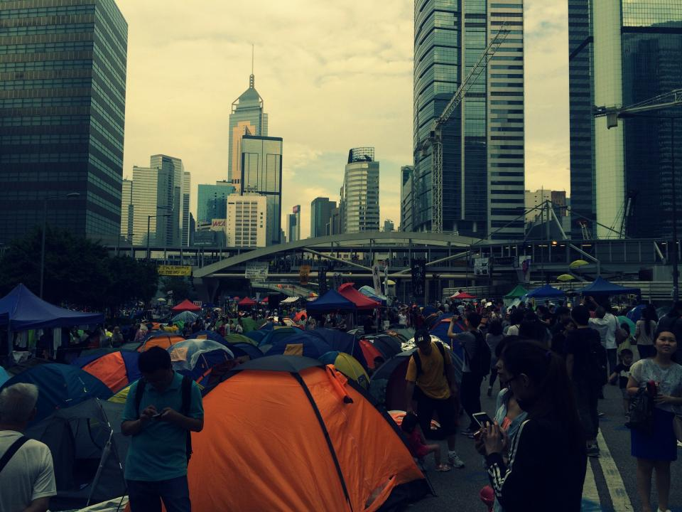 hong kong protest tents people streets crowd busy buildings city architecture towers