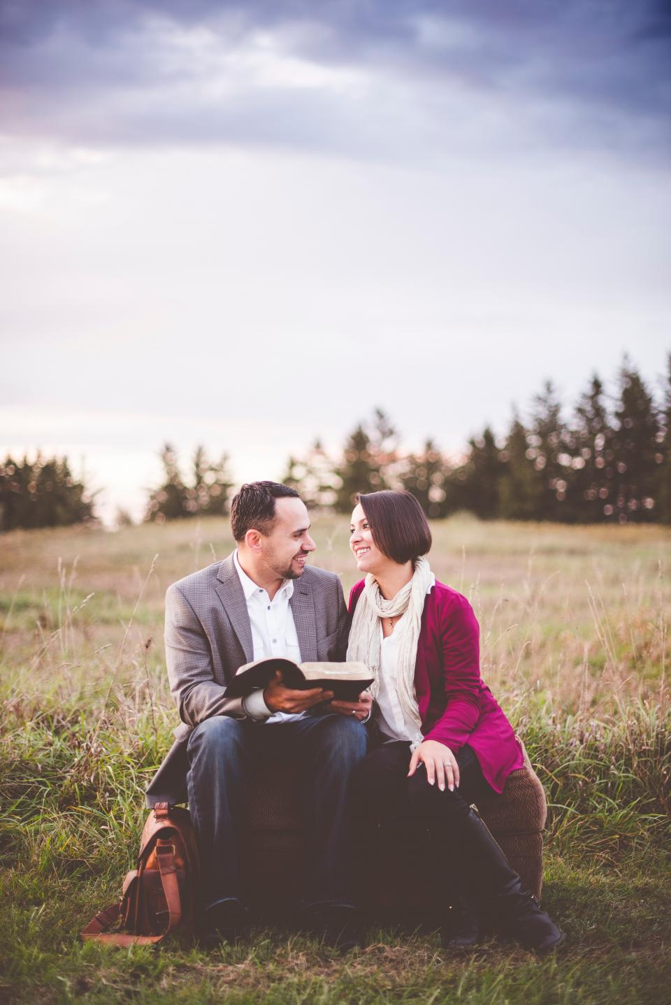 people couple man woman smile happy sitting green grass book bible reading outdoor trees plants sky clouds
