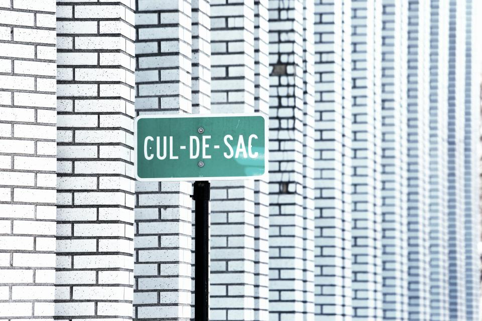 cul-de-sac street sign white bricks architecture