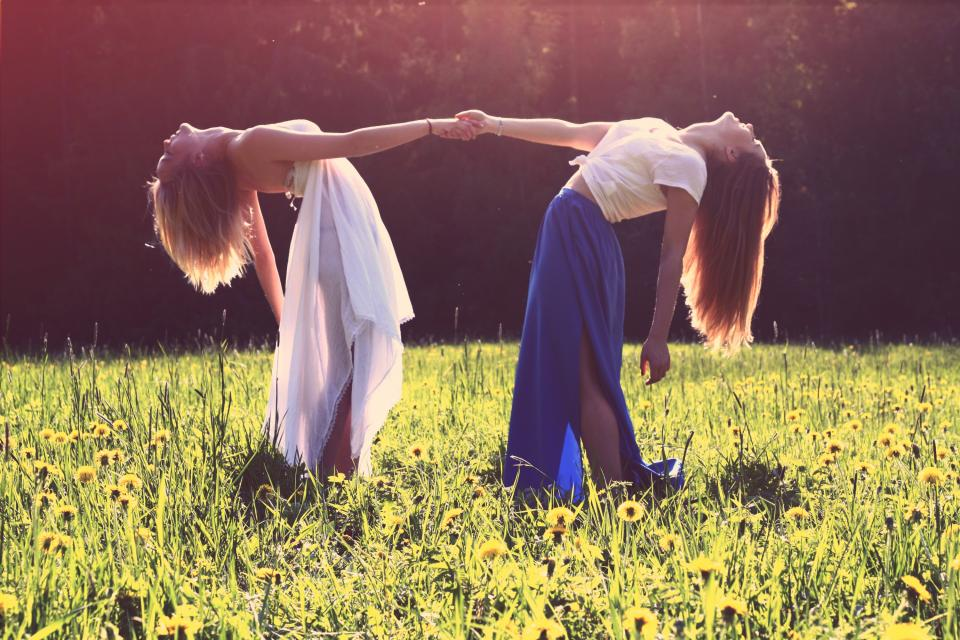girls friends holding hands dress fashion long hair sunset field flowers grass people beauty smile smiling happy fun