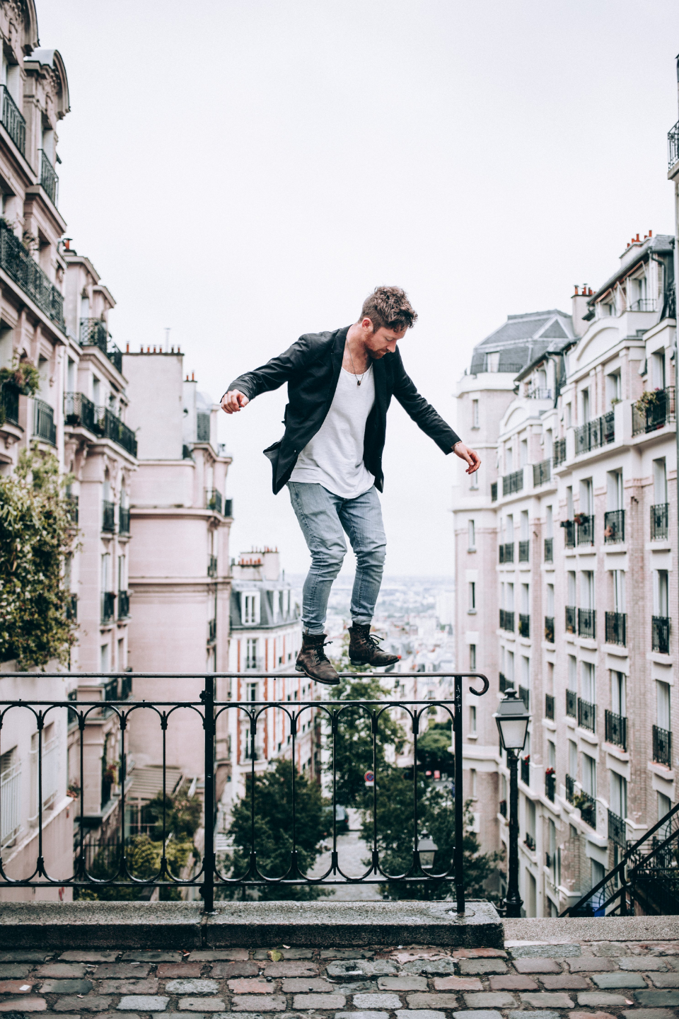 man fashion balancing city buildings standing person architecture outdoors risk daring urban stairs cobblestone male