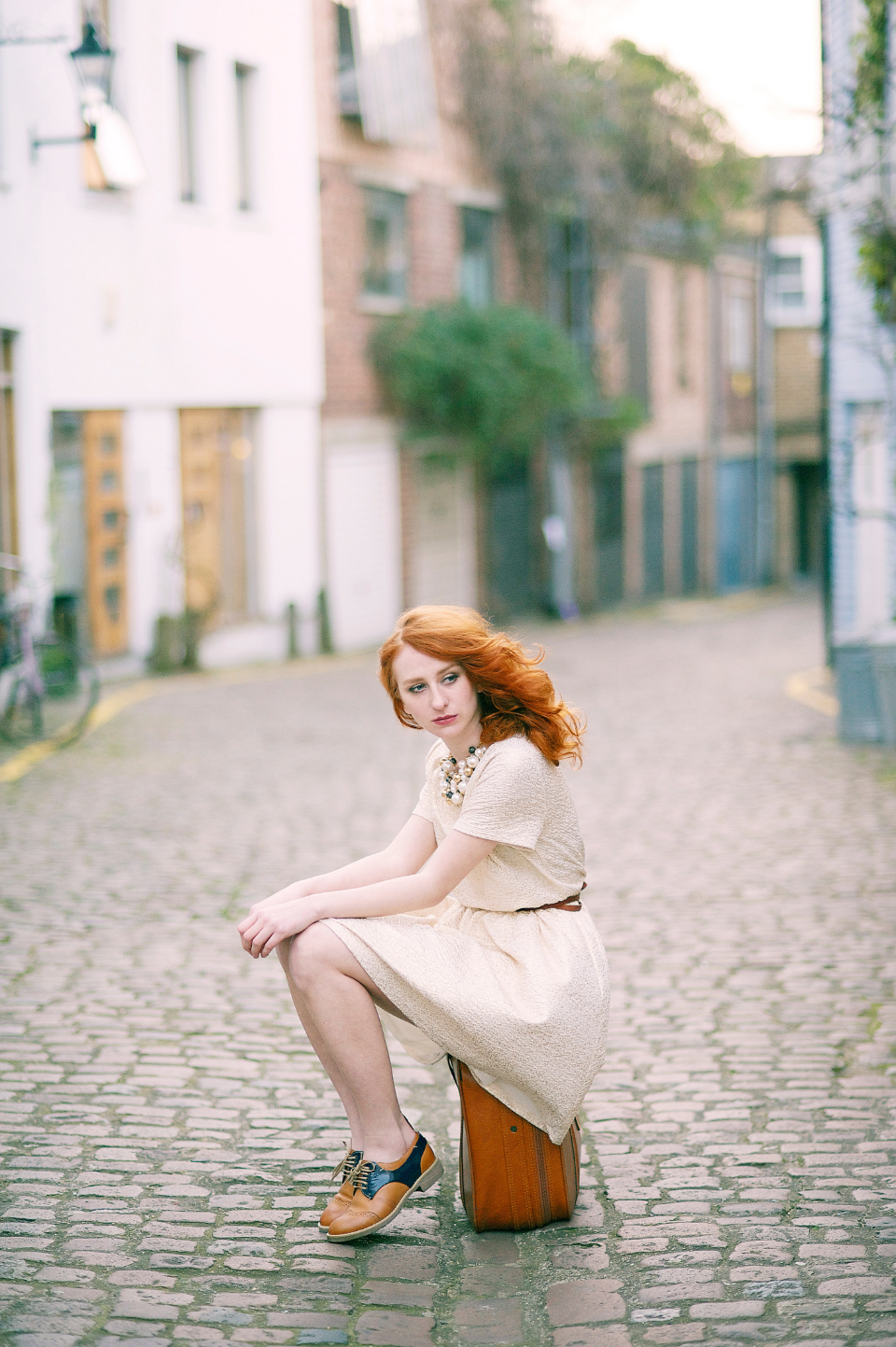 fashion model sitting suitcase street cobbles red haor girl female attractive daylight people travel