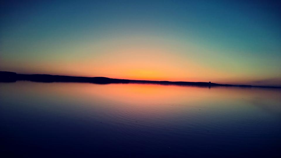 nature water ocean sea still calm surface sky clouds land silhouette gradient blue yellow pink beautiful majestic
