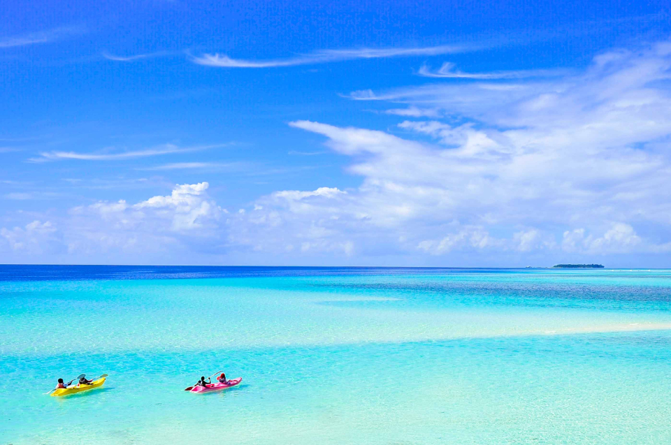 Maldives Couple travel honeymoon wedding holiday canoe beach lagoon ocean sky blue turquoise island atoll cloud shades of blue paddle paddle boat