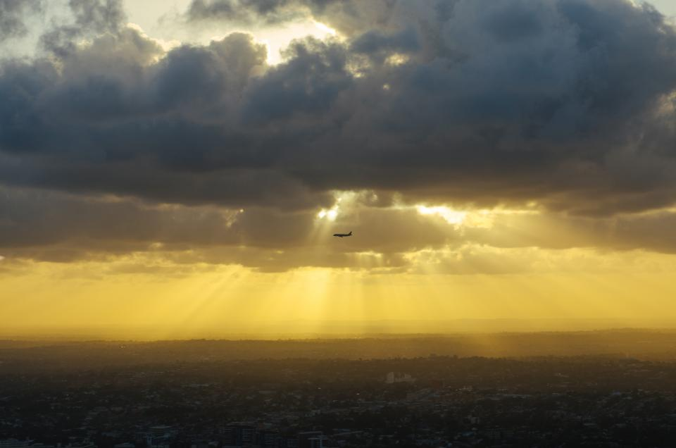 sunbeams clouds airplane flying travel transportation sunrise dawn cloudy