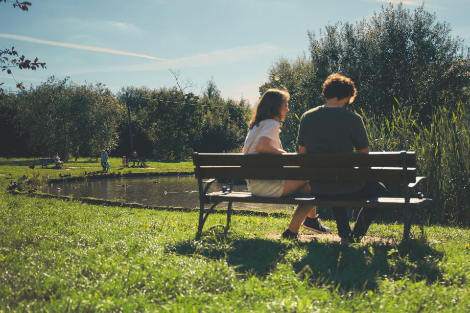 couple people girl guy sitting bench dating green grass nature lake water trees sunny sunlight summer sky cloud