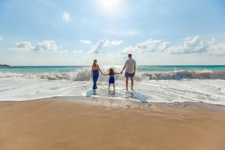 people family woman man mother father kid girl baby child beach sea water ocean vacation summer sunny sky clouds waves