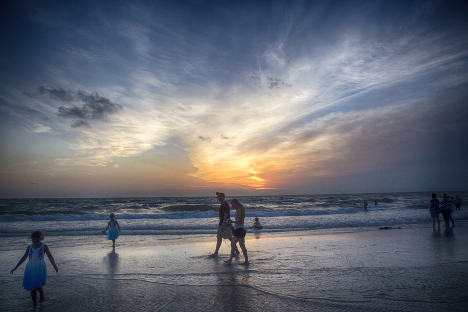 beach sunset florida ocean people children play clouds sand evening